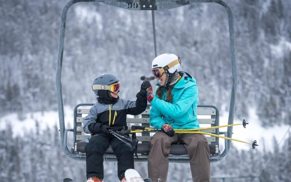 A parent and young child wearing ski gear high-five each other while sitting on a skit chair lift, with a snowy landscape behind them.