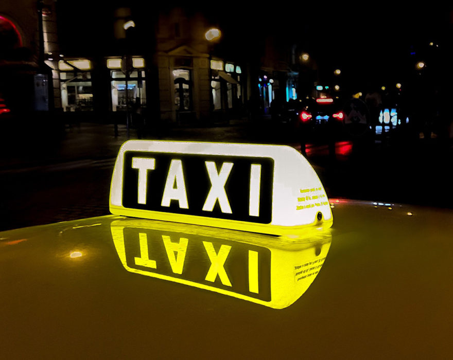 A taxi sign is lit up on top of a car