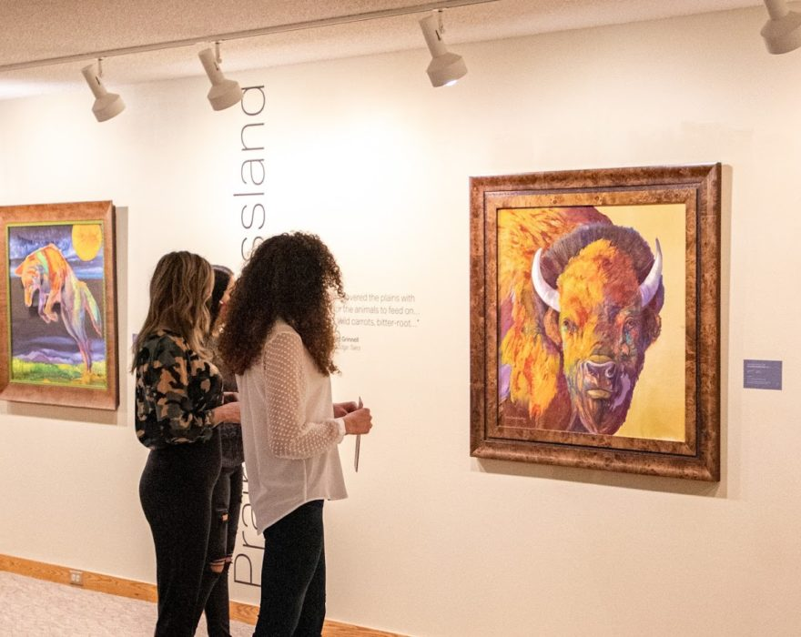 Three women look at artwork in a local museum in Great Falls, MT