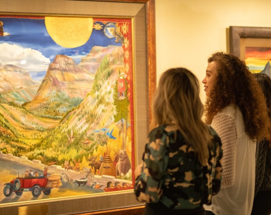 Three women look at a painting in a gallery