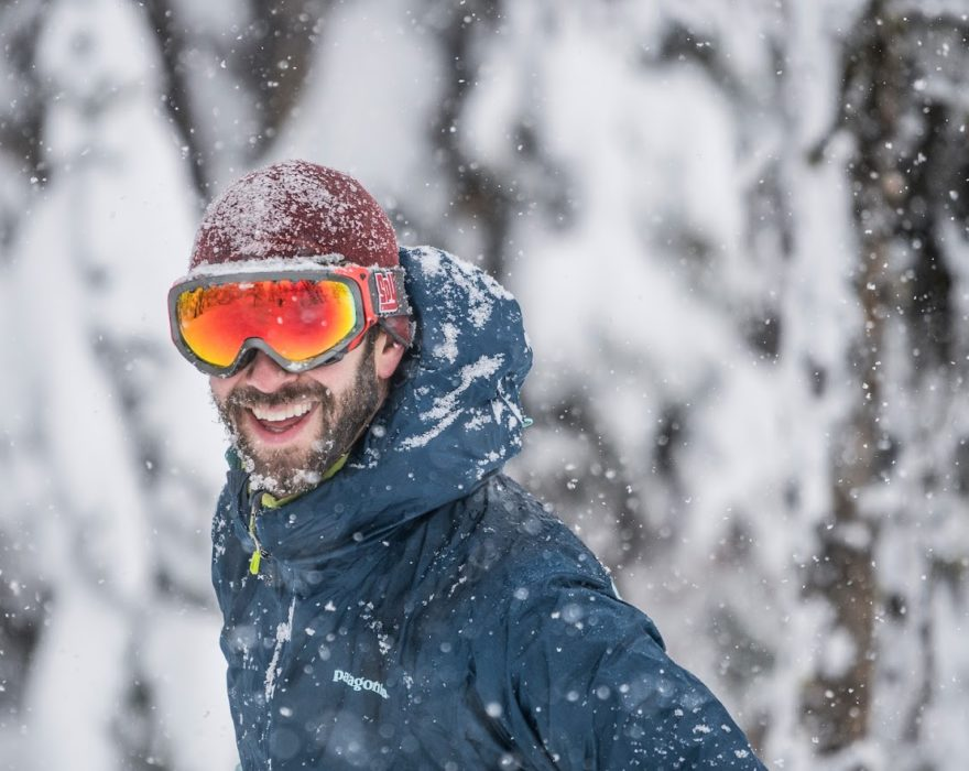 A man wearing orange tinted snow goggles smiles for a photo with a snowy background behind him in Great Falls, MT