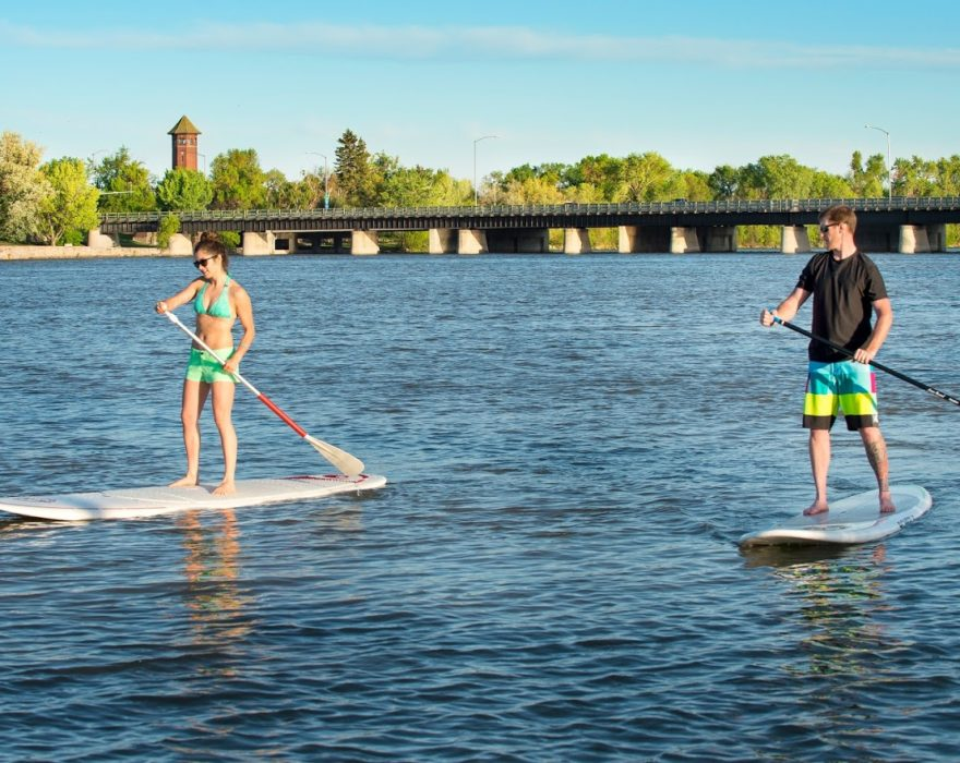 Two people paddleboard on a river in Great Falls, MT