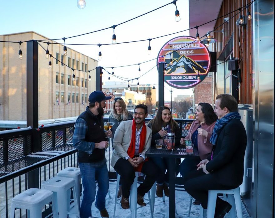 A group of friends gathers for drinks on an outdoor restaurant patio