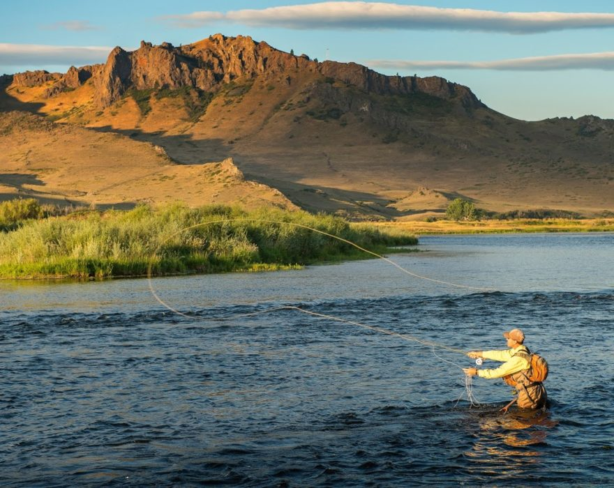A man wades into the middle of a river in Great Falls, MT to go fly fishing