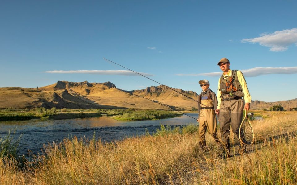 A father and son carry fishing poles through a grassy area next to a river, with mountains in the background in Great Falls, MT