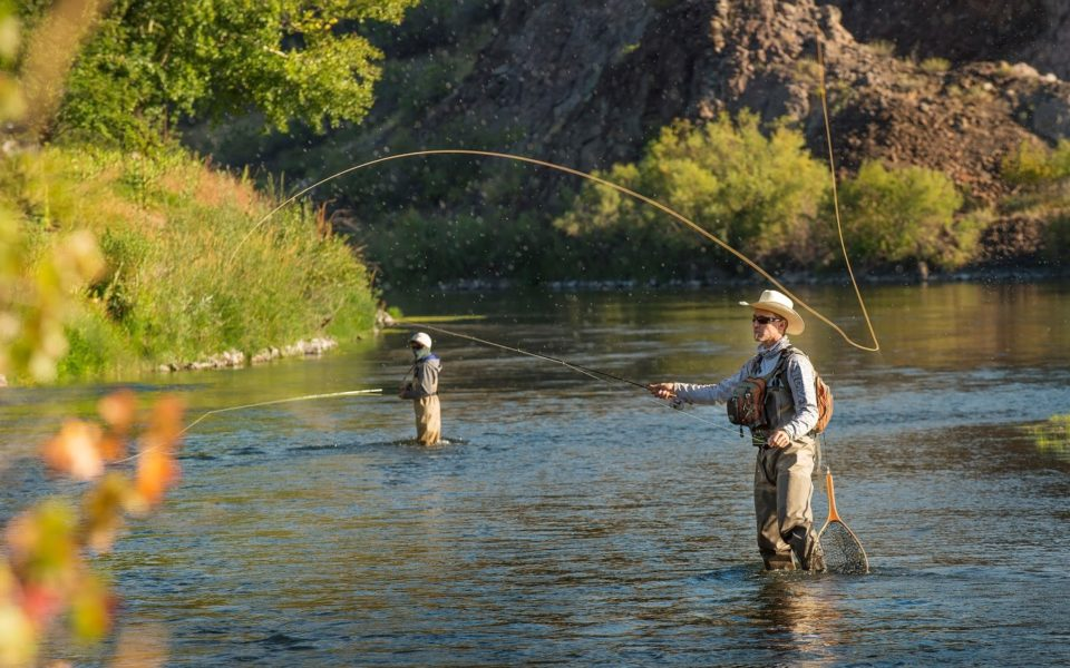 Two men, one wearing a cowboy hat, wade up to knee height in the middle of a river while fly fishing on a sunny day in Great Falls, MT