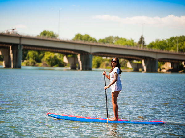 A young woman uses a stand up paddle board as she travels down a river in Great Falls, MT