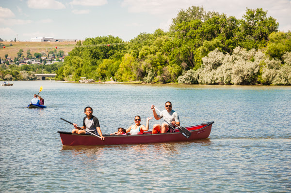 A family paddles a canoe down a river in Great Falls, MT