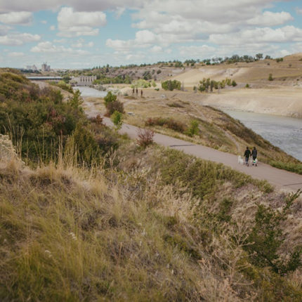Two people walk their dog on a wide, flat trail next to a scenic river and hilly landscape in Great Falls, MT