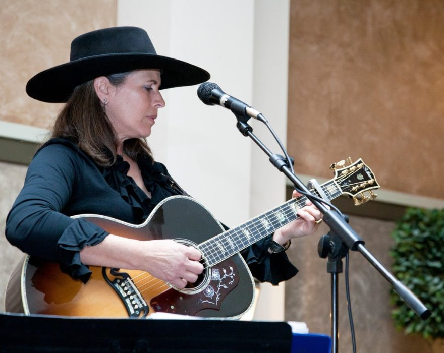 A woman wearing a cowboy hat plays guitar
