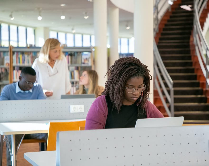 A college student types on her laptop in a media library