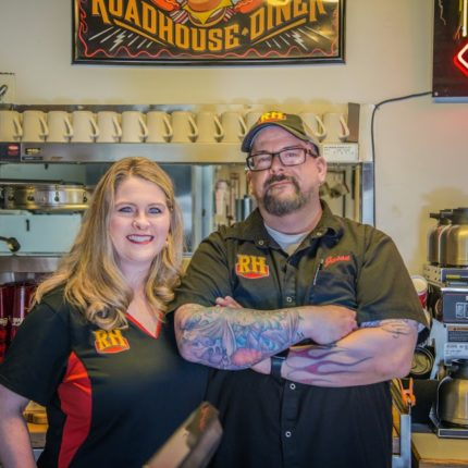 A man and woman pose in front of the Roadhouse Diner sign in Great Falls, MT