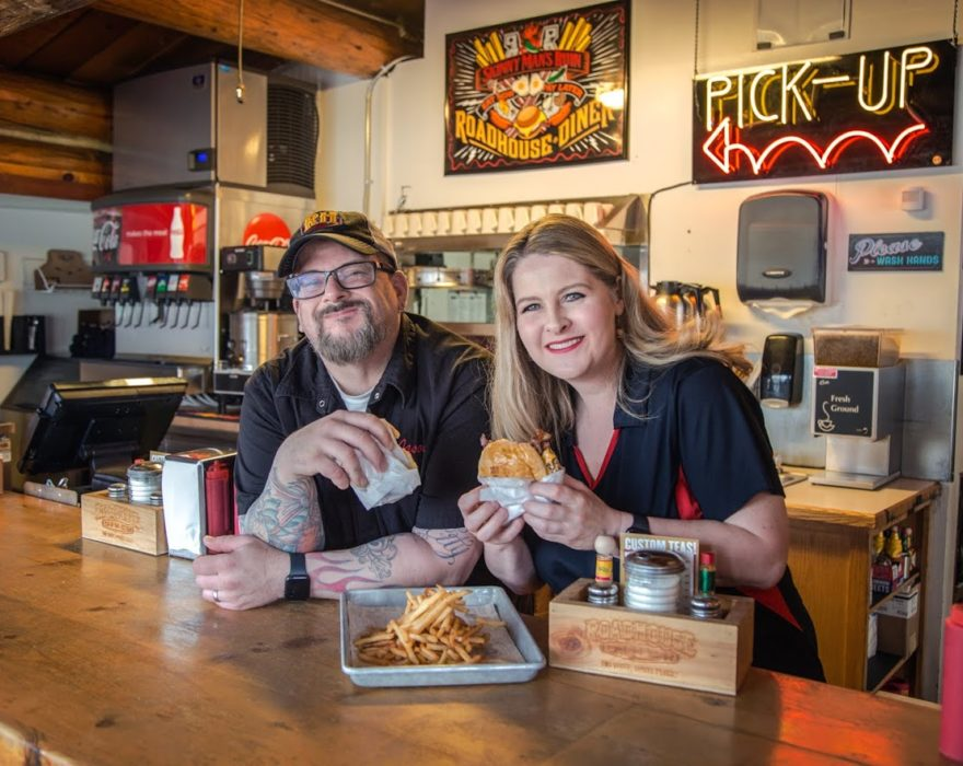 A man and woman pose with burgers and fries at Roadhouse Diner