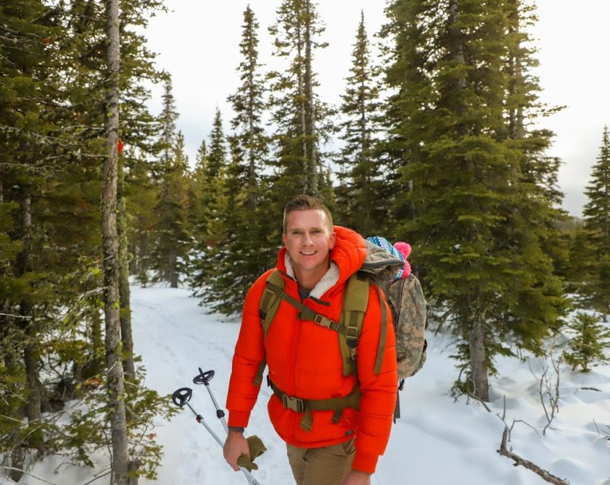 A man wearing an orange winter coat stops to smile for a photo in front of a background of snow and pine trees in Great Falls, MT