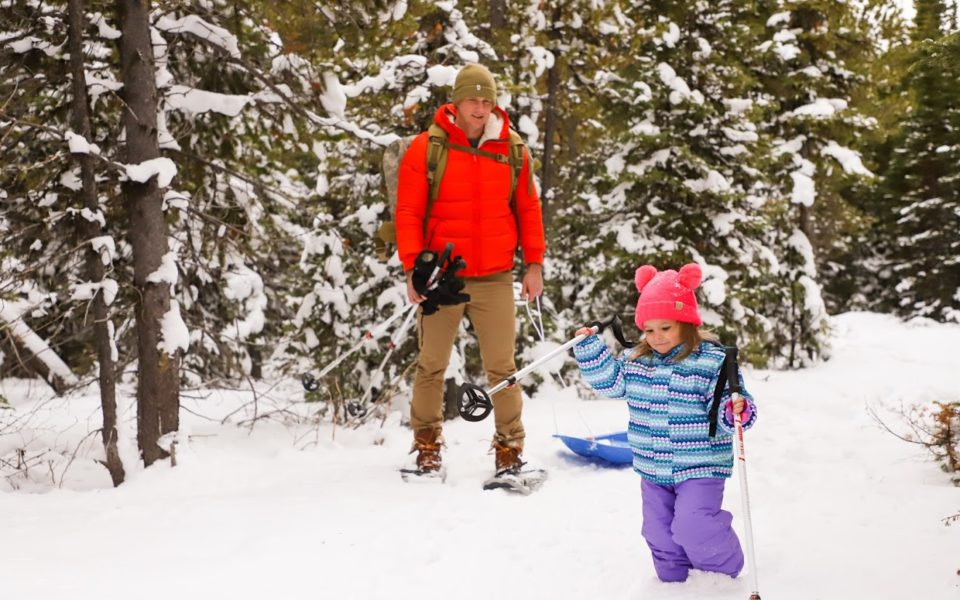A child and her father use ski poles for support as they walk through the snow, with the father carrying a sled behind them
