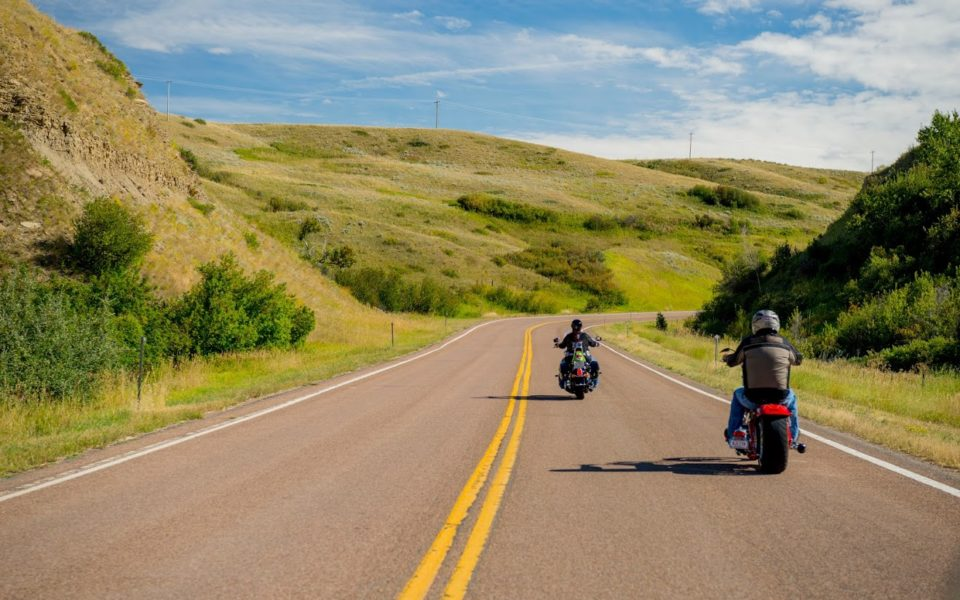 Two motorcyclists drive down a long, winding road with a landscape of green hills rising up in the background