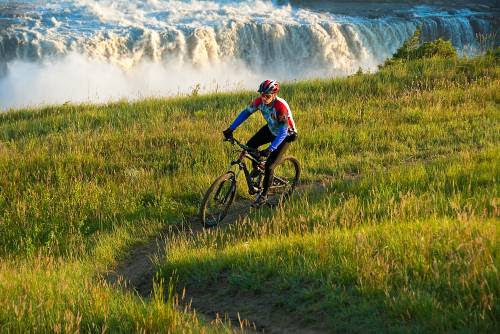 A man wearing a helmet and mountain biking gear bikes on a grassy trail next to a waterfall in Great Falls, MT