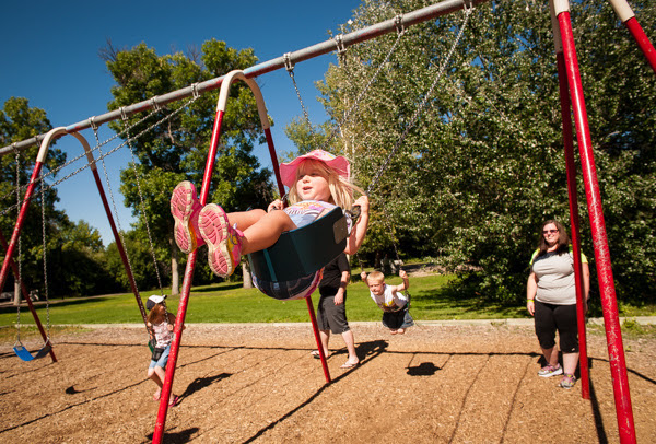 A young girl wearing a pink hat swings on a swingset