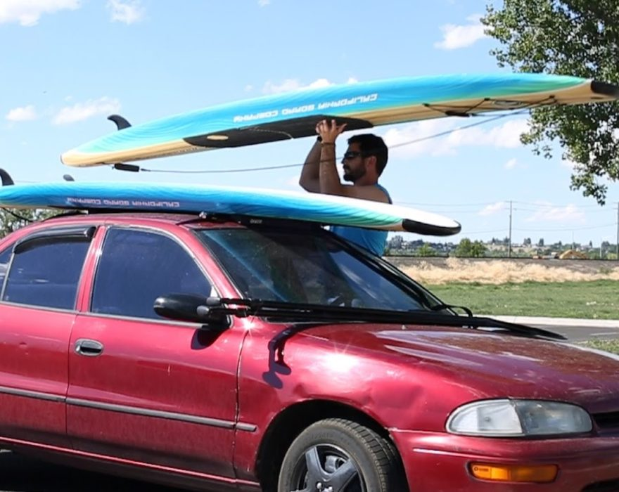 A man loads paddleboards on top of his car