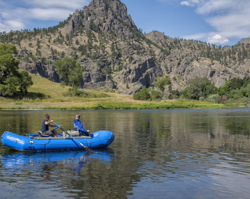 Two people use a boat to navigate down a river in Great Falls, MT