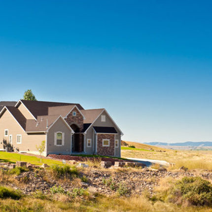 A house in Great Falls, MT sits on many acres of land with vast hills in the background